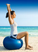 Woman doing pilates on the beach — Stock Photo