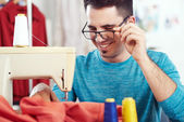 Fashion designer working on sewing machine — Stock Photo