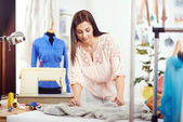 Female designer measuring textile material — Stock Photo