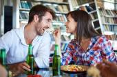Couple eating spaghetti and cheers with beer — Stock Photo