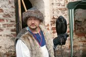 "Unidentified man with raven on glove attends annual historical military Festival  ""Kirillo-Belozerki siege,"" Kirillo-Belozerki museum-reserve, Kirillov town, Vologda region, Russia — Stock Photo"