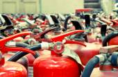 The fire extinguisher used. background with a lot of fire extinguishers — Photo