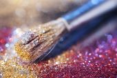 Close-up on makeup brush and colorful shining powders — Stock Photo