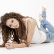 Beautiful girl with long curly hair wearing white top and torn jeans — Stock Photo #56815135