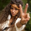 Beautiful hippie girl in the park making the sign of peace — Stock Photo #56817339