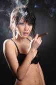 Hot sexy woman with bra smoking cigar. Shrouded in smoke — Stock Photo