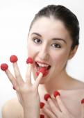 Young sexy woman eating raspberries off fingers — Stock Photo