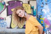 Happy hip teenage blonde girl standing by graffiti wall — Stock Photo