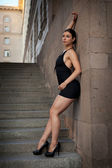 Young sexy woman with black dress posing of stairs — Stock Photo