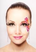 Woman with creative colorful makeup using false eyelashes — Stock Photo