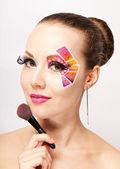 Woman with creative colorful makeup using false eyelashes holding makeup brush — Stock Photo