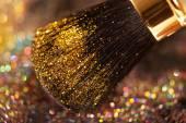 Closeup on makeup golden brush and shining powder — Stock Photo
