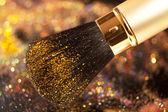 Closeup on makeup golden brush and shining powder — Stock Photo