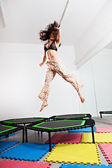 Jumping brunette woman on a trampoline — Stock Photo