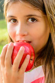 Little girl is eating a red apple — Stock Photo