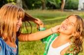 Seven year olds pooling each others hair — Stock Photo