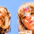 Two sisters blowing bubbles — Stock Photo #57524461