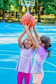 Seven year old girls  playing basketball — Stock Photo