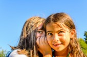 Two little girls  playing and whispering secrets in the park — Stock Photo