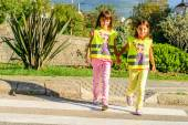 Little elementary school kids crossing the street wearing a vest with the stop sine on it — Stock Photo
