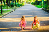 Two little girls  drowing with chalk in the park — Stock Photo