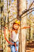 Little girl climbing in adventure park — Stock Photo