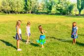 Four little girls  playing elastics in the park — Stock Photo
