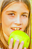 Beautiful nine year old girl  eating apple — Stock Photo