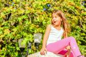 Seven year old girl  sitting on the wall — Stock Photo