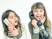Two seven year old girls talking on the old vintage phones with  — Stock Photo