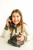 Seven year old girl with old vintage phone before white backgrou — Stock Photo