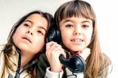 Seven year old girl talking on the old vintage phone and her sis — Stock Photo