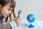 Concentrated seven year old girl examining globe with a loupe — Stock Photo