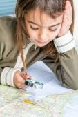 Concentrated seven year old girl examining the map with a loupe — Stock Photo