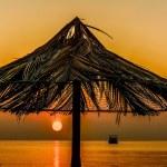 Beach umbrella on sunset over the see — Stock Photo #73010881