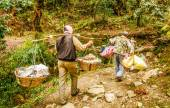 Man in Nepal  carrying a big heavy load on their shoulders — Stock Photo