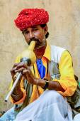 A snake charmer is playing the flute to the snake — Stock Photo
