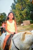 Beautiful eight year old girl on the horse — Stock Photo