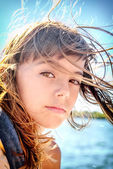 Portrait of a beautiful eight year old girl with the wind blowin — Stock Photo