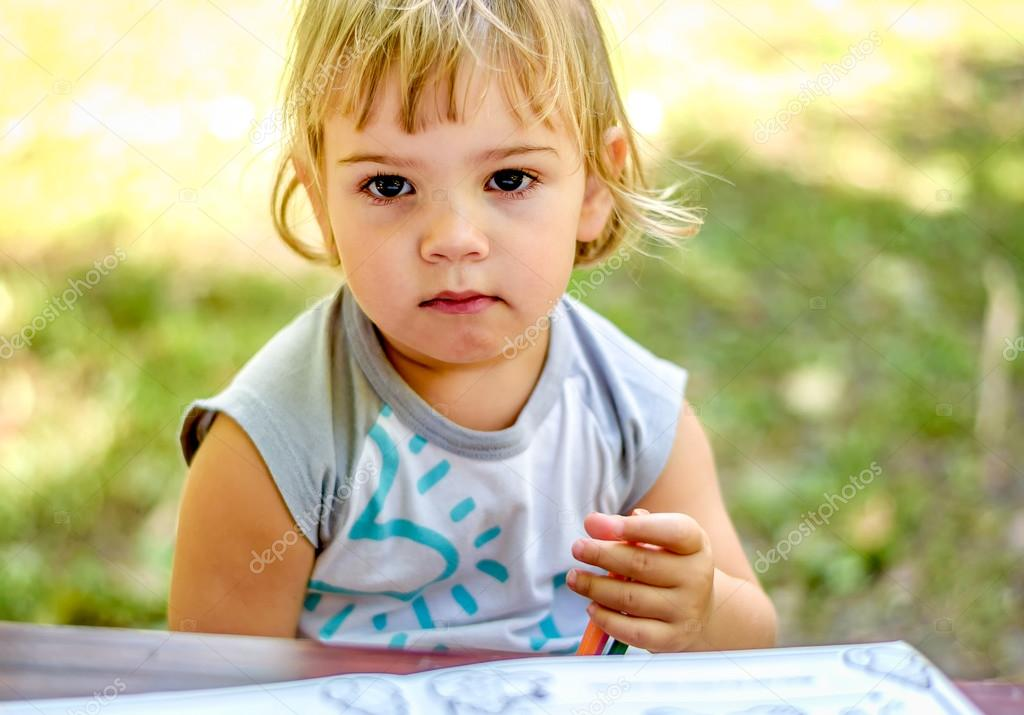 Beautiful Two year old girl drawing in a coloring book Stock