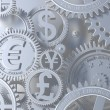 Silver clockwork with gears like currency sign. Euro gear, dollar, yen, pound — Stock Photo #56589609