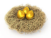 Three Easter golden eggs in a nest. — Foto de Stock