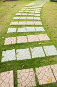 Colorful cement walkway on green grass — Stock Photo