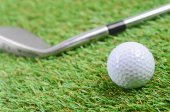 Iron and golf ball on green grass field — Stock Photo