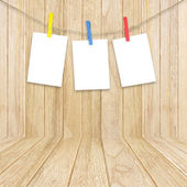 Empty white photo frames hanging with clothespins on wooden back — Stock Photo