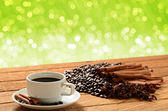 A cup of coffee on wooden table with green bokeh background — Foto de Stock