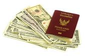 Thailand passport and roll of dollars money on white background — Stock Photo