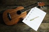 Guitarra cavaquinho com nota de música em branco e caneta — Fotografia Stock