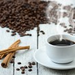 Coffee cup with smoke and coffee beans around — Stock Photo #60130133