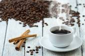 Coffee cup with smoke and coffee beans around — Stock Photo
